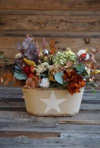 Centro de flores secas y preservadas en un recipiente metálico