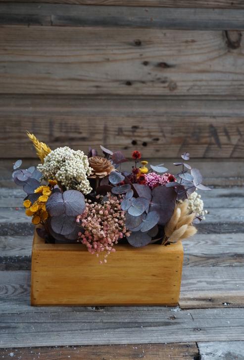 Centro de flores secas y preservadas en una caja de madera barnizada