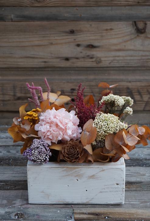 Centro de flores secas y presrvadas en una caja de madera pintada de blanco