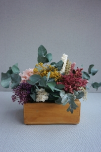 Centro de flores en caja de madera barnizada