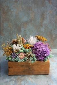 Centro de flores en caja de madera con base de piña