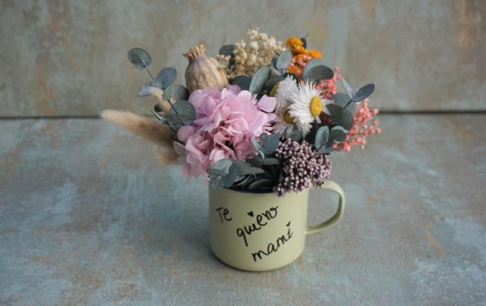 Centro de flores secas y preservadas en una taza