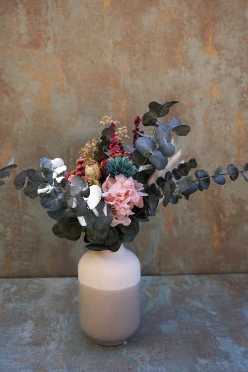 Jarrón de cerámica con base de eucalipto y flores preservadas