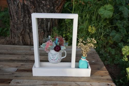 Centro de flores en una taza y una botellita con paniculata blanca