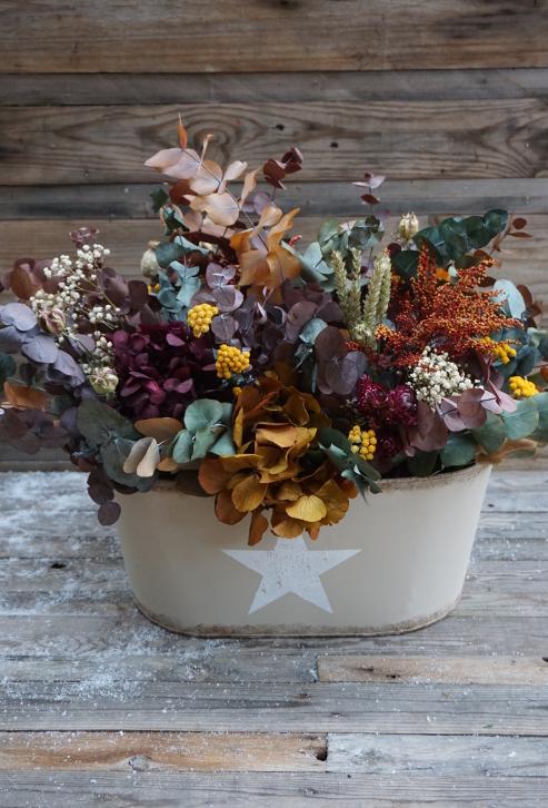 Centro de flores en un recipiente metálico con base de eucalipto preservado