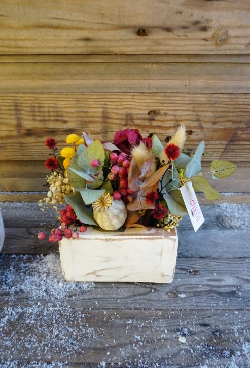 Centro de flores secas y artificiales en una caja de madera