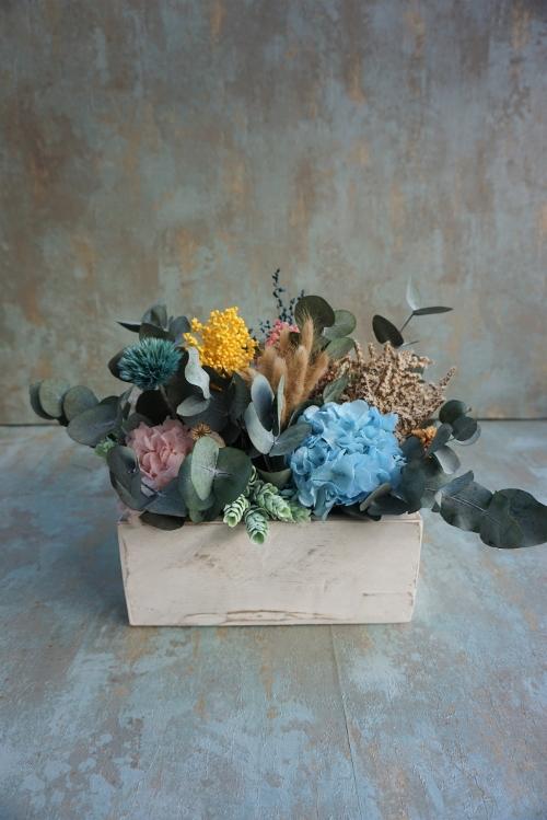 Centro de flores en recipiente artesanal de madera