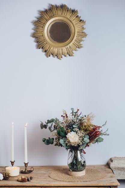 Centro de flores preservadas en jarrón de cristal con base de madera
